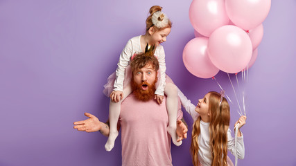Indignant foxy father left alone with small children, plays with daughters, organizes real party for children, has uncertain expression. Two female kids play together, hold pink air balloons