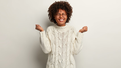 Half length shot of optimistic female feels like winner, raises hands in fists, dressed in white knitted sweater, closes eyes from pleasure isolated over white background. People, success, joy concept Wall mural