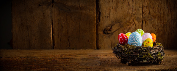 Colorful painted happy easter eggs in birds nest basket on rustic wooden old panorama background copy space