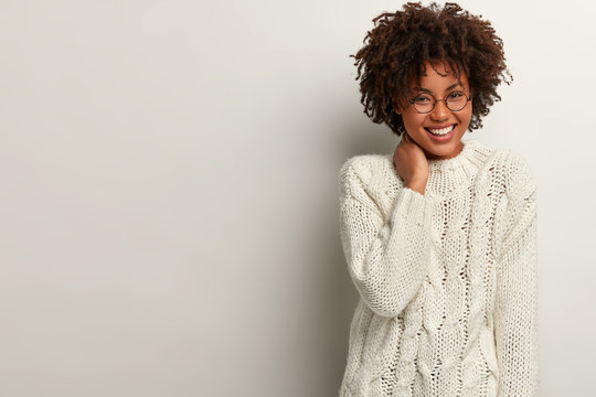 Glad laughing curly woman giggles as heard funny joke, wears white sweater, keeps hand on neck, expresses positive emotions, stands indoor, blank space right for your advertisement. Happiness