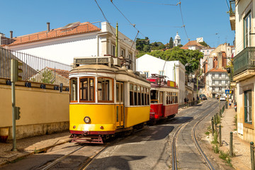 Keuken foto achterwand Milan Yellow and red vintage trams on old streets of Lisbon, Alfama, Portugal, popular touristic attraction and destination.