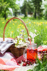 Cherry juice in mason jar and picnic basket with food, flowers.