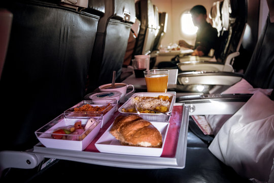 Lunch in airplane. Inflight economy class meal on tray: butter, bread, chicken salad. Fruits: watermelon, pineapple and gold kiwi. Hot dish: rice with vegetables and beef.