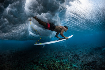 Surfer dives under the breaking wave in the tropics