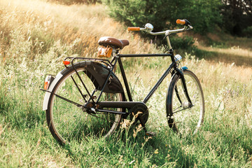 retro bike in black standing in a field, hipster style