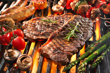 Delicious grilled meat with vegetables sizzling over the coals on barbecue
