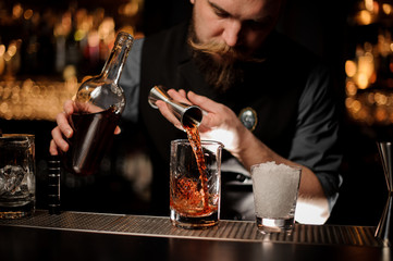 Bartender pouring a brown alcohol to the cocktail from the steel jigger