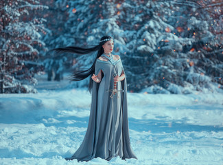 charming attractive lady in snowy forest, militant elf princess with black long flying hair holds sword, loose gray warm dress and raincoat in sparks of fire in winter, creative cold blue colors