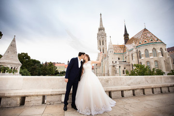 Young beautiful stylish pair of newlyweds kissing by the Fisherman's Bastion in Budapest, Hungary