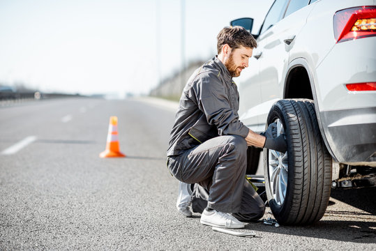 Handsome road assistance worker in uniform changing car wheel on the highway