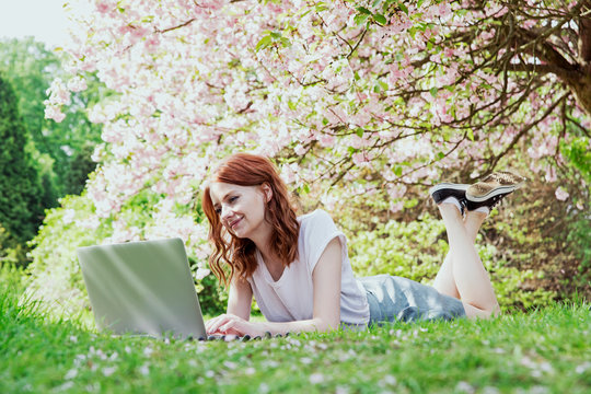 Young smilling hipster redhead girl working on her laptop in blossom cherry trees garden. Blogger preparing posts for social media in the garden of cherry blossoms. Spring time. Template. Blank.