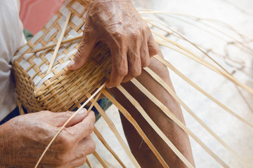 Senior man hands manually weaving bamboo.