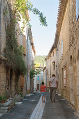 Father and son walking through the old narrow street of Lagrasse, France.
