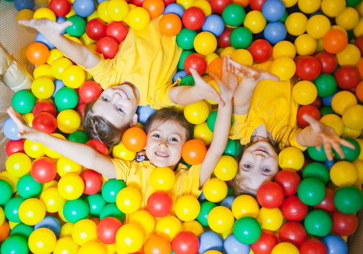 Three happy little kids girls in ball pit smiling happily at camera while having fun in children play center. Top view