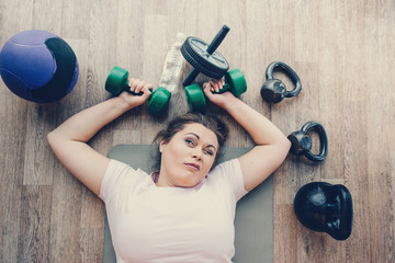 Fat woman lying exhausted on floor in fitness club