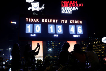 People take pictures in front of a countdown clock decoration for the upcoming general election at Bundaran Hotel Indonesia roundabout in Jakarta