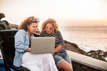 Couple of people women friends use together a laptop computer sitting on the back of convertible car and sunset on the ocean in background - work everywhere and travel vacation plan concept