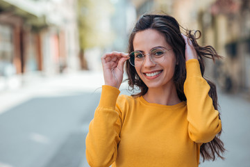 Headshot of a positive young woman with eyeglasses in the city, smiling at camera.