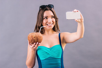 Portrait of cheerful young woman in swimsuit taking selfie on her smart phone while standing isolated on gray background. Happy beautiful girl in stylish swimwear making photo with cocktail in coconut
