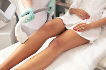 Legs of woman and laser hair removal procedure