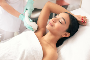 Smiling woman undergoing laser hair removal on her armpit
