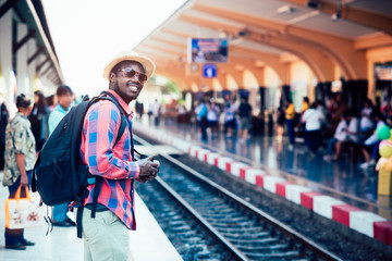 African man traveler standing waiting for the train on railroad station Wall mural