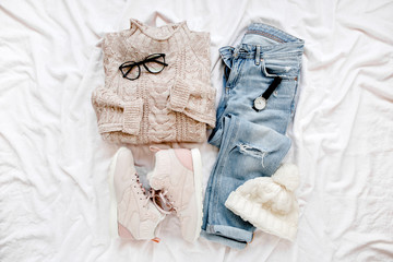 Wall Mural - Woman clothes and accessories set on white background. Women's warm sweater, jeans, sneakers, glasses. Modern and casual outfit. Shopping concept. Fashion blog or magazine concept. Flat lay, top view
