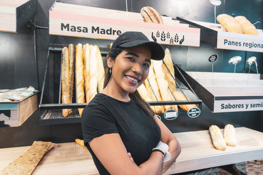 Beautiful latin woman serving bread in pastry shop.