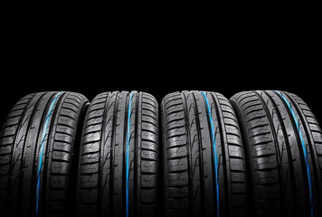 Studio shot of set of summer car tires on black background. Tire stack background. Car tyre protector close up. Black rubber tire. Brand new car tires. Close up black tyre profile. Car tires in a row