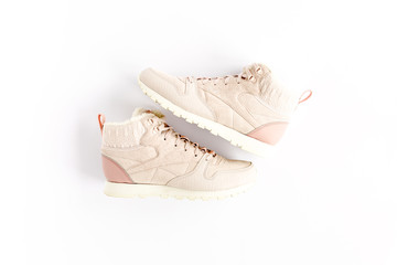 Wall Mural - Pastel pink female sneakers on white background. Flat lay, top view minimal background. Fashion blog or magazine concept.