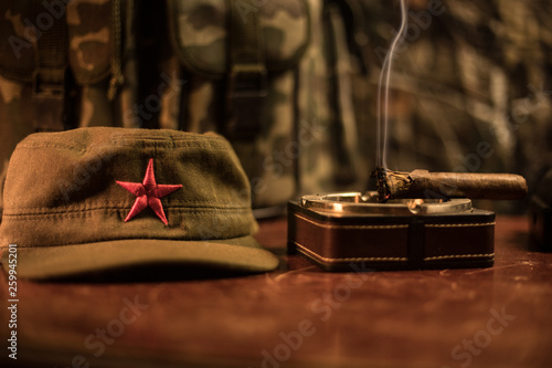 a961f1de8f6 Close up of a Cuban cigar and ashtray on the wooden table. Communist  dictator commander table in dark room. Army general`s work table concept.