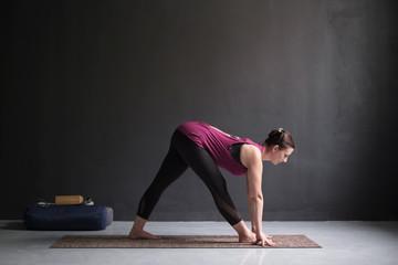 woman practicing yoga, doing Half Pyramid or Parshvottanasana