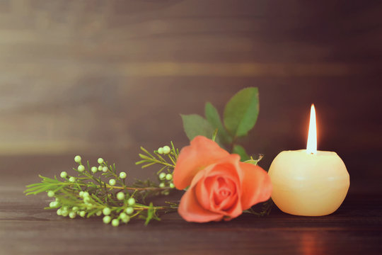 Burning candle and flowers
