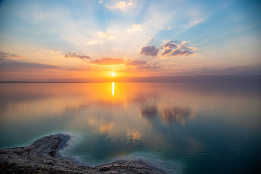 Amazing sunset over Dead sea, view from Jordan to Israel and Mountains of Judea. Madaba governorate and Karak governorate. Reflection of sun, skies and clouds. Salty beach, salt on Dead sea coast