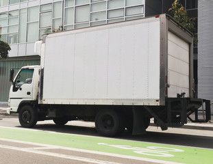 Refrigerated food delivery van in city traffic with green marked bike lane.