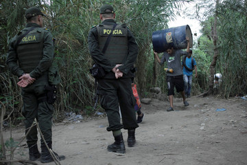Colombian police officers stand guard as people walk on a pathway near the Tachira River on the Colombian-Venezuelan border on the outskirts of Cucuta