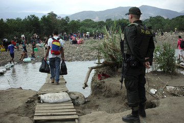 A Colombian police officer stands guard close to people walking on makeshift bridges to cross the Tachira River on the Colombian-Venezuelan border, as seen from the outskirts of Cucuta