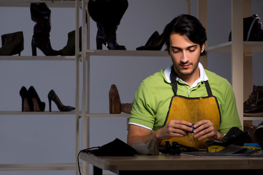Young shoemaker in workshop at night