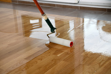 Obraz Lacquering wood floors. Worker uses a roller to coating floors. - fototapety do salonu