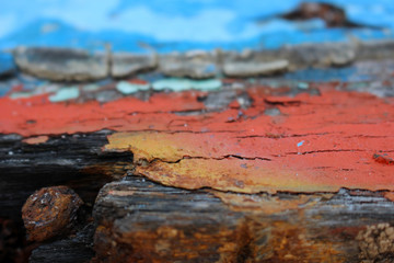 Close up detail of an old boat's hull forms an abstract textured background of old decaying wooden boat panels with orange, red and sky blue peeling paint.