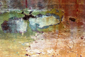 Abstract textured background of an old decaying wooden boat hull with mostly red and orange color peeling paint.