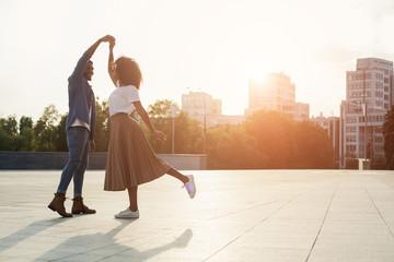 Loving couple dancing at sunset on the street