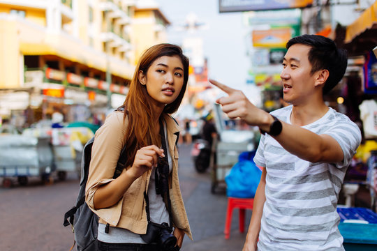 Young female tourist asking for directions and help from local people in Bangkok, Thailand