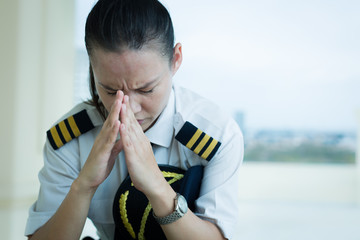 Stressed out female pilot worried at work.
