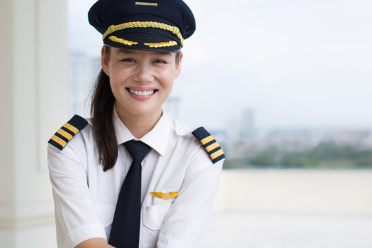 Portrait of a pretty female pilot smiling.