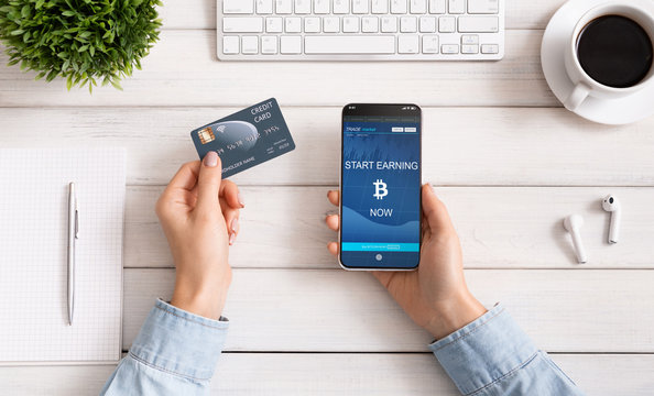 Woman using credit card and bitcoin earning mobile app