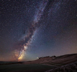 Vibrant Milky Way composite image over landscape of ancient chalk white horse at Cherhill in...