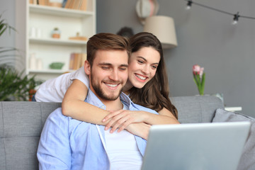 Young couple doing some online shopping at home, using a laptop on the sofa.