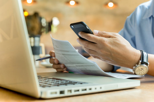 Business man using cell phone and holding document with laptop on table.
