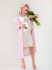 portrait of pregnant woman  hiding her face with a bunch of pink flowers